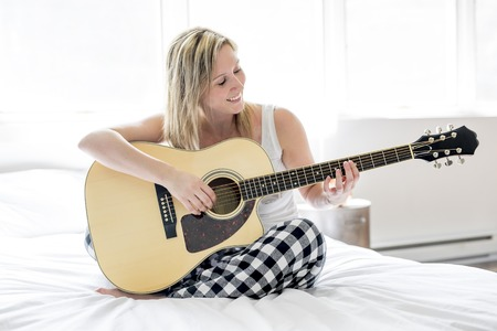 Smiling woman with guitar sitting on the bed Stock Photo