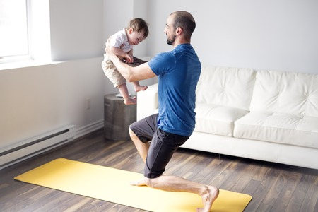 sports man is engaged in fitness and yoga with a baby at home
