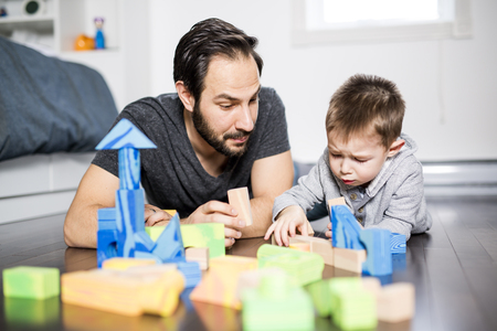 cute child playing with color toy indoor with is dad