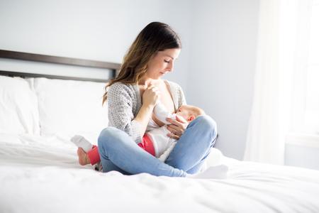 Jonge moeder die haar babykind houdt. Moeder die baby verzorgt. Stockfoto