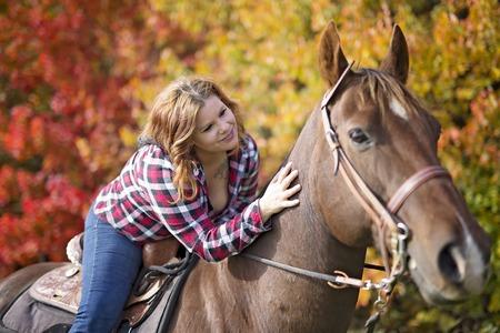 屋外の馬で美しく、自然な大人の女性