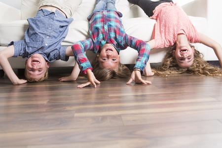 three childs laying upside down on a white sofa at home funny