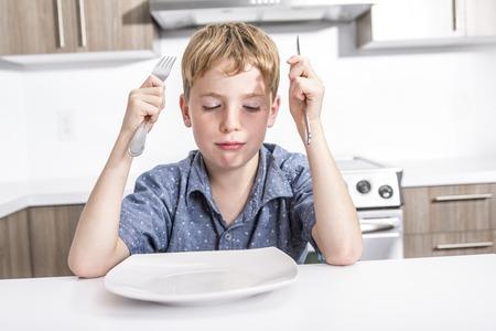 Kleine jongen met verveelde knorrige uitdrukking bij een tafel zitten