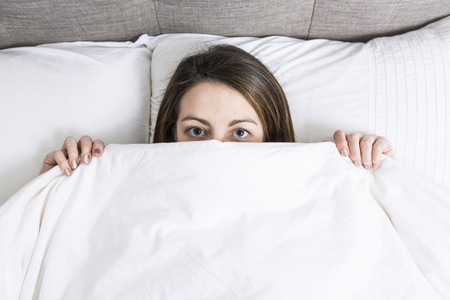 A Young sleeping woman in bedroom at home wearing in white Stock Photo