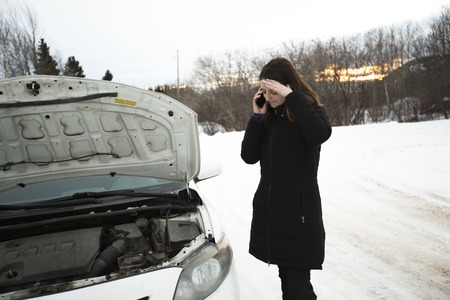 girl on the winter road is calling the phone near the car Reklamní fotografie