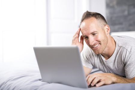 Serious casual young man using laptop in bed at home Foto de archivo