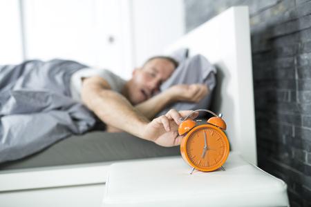 Tijd om wakker te worden. Moeide man in het bed