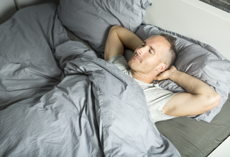 Portrait of a young man from above sleeping in  bed. Stock Photo