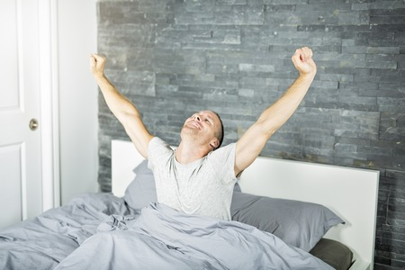 Cheerful young man waking up in bed and stretching his arms 版權商用圖片