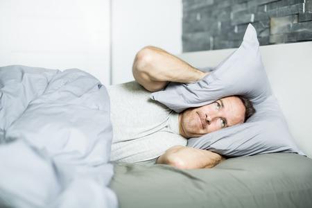 Moeide man in het bed Stockfoto