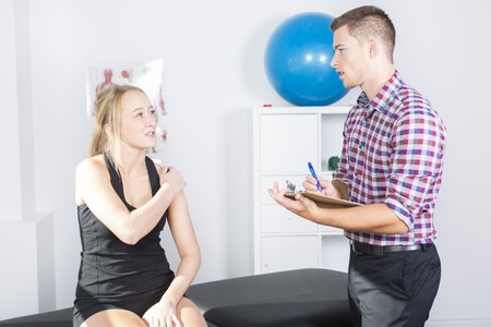 male physio therapist and woman helping patient Standard-Bild