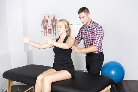 male physio therapist and woman helping patient Stock Photo