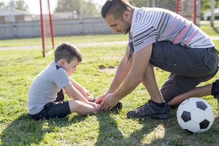 man with child playing football on field Reklamní fotografie