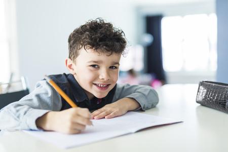 A Cute little boy doing homework at home
