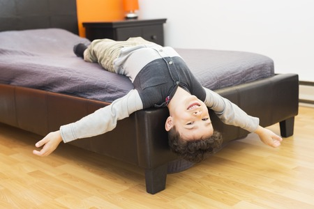 A Playful little boy in bed upside down Stock Photo