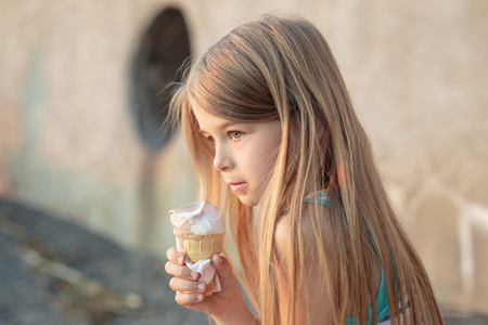 A Beautiful little girl eats ice-cream in the summer