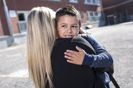 A Boy and his mother hugging outside at school