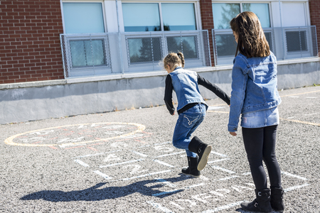 Hopscotch on the schoolyard with friends play together