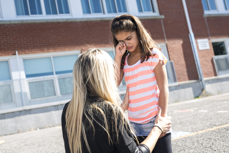 teacher consoling a girl on  schoolyards