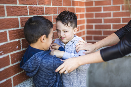 놀이터에서 싸우는 두 소년 멈추는 교사 스톡 콘텐츠