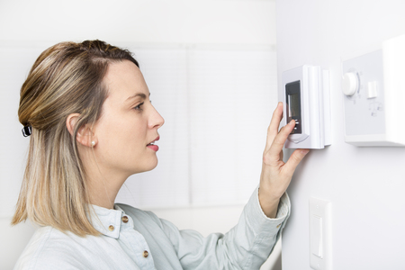woman set the thermostat at house. Stock Photo