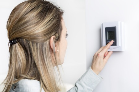 mujer establece el termostato en la casa. Foto de archivo