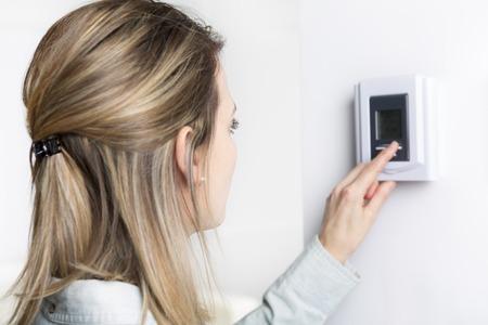 vrouw zet de thermostaat in huis.
