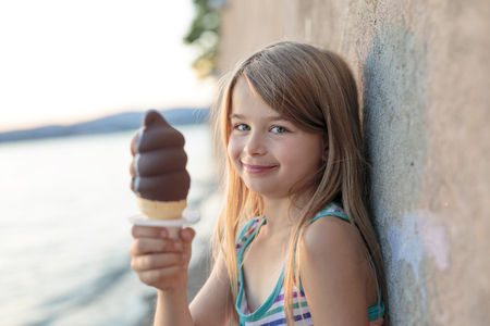 Beautiful little girl eats ice-cream in the summer