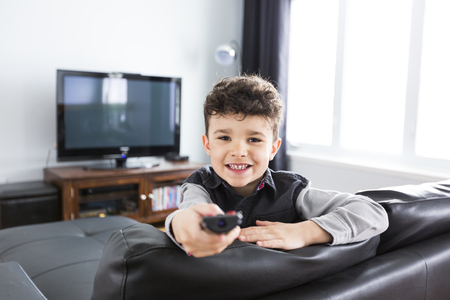 little boy watching TV lying in the living-room Archivio Fotografico
