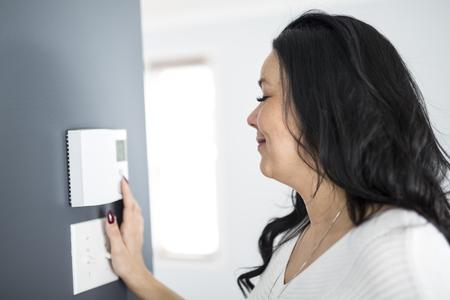 Woman programming temperature inside home