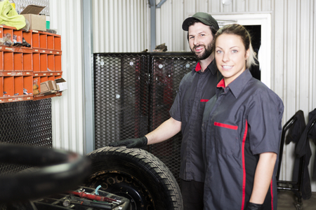 Mechanic woman and men working team in his shop