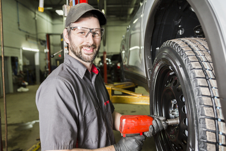impact wrench: Mechanic working on car in his shop