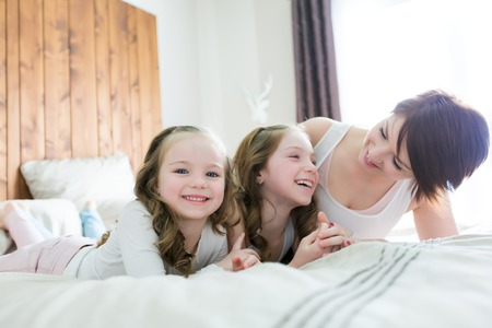 Mother and two children in the bedroom on the bed