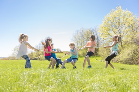 Group of child have fun on a field with rope Stock Photo