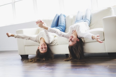 closeup portrait of hugging 2 beautiful young women having fun on sofa Stock Photo