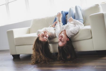closeup portrait of hugging 2 beautiful young women having fun on sofa Stock Photo