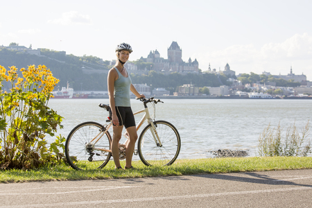 Young Woman Riding Bike outside with quebec view Stock Photo