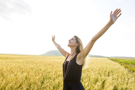 Happy, satisfied young woman standing in the wheat field. Stock Photo