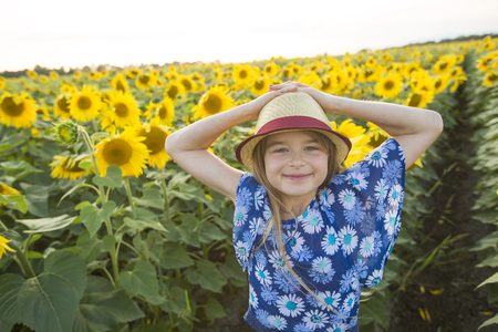 happy girl on a field of sunflowers on summer sunset