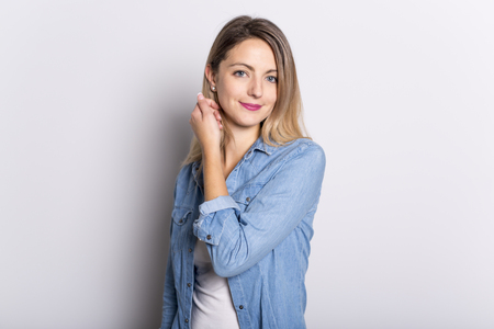 Young Woman in Denim Shirt and Jeans, Leaning Against Gray Wall Background