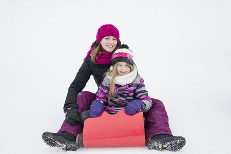 little girl riding on snow slides in winter time Stock Photo