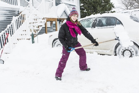 snowdrifts: woman shoveling and removing snow outside Stock Photo