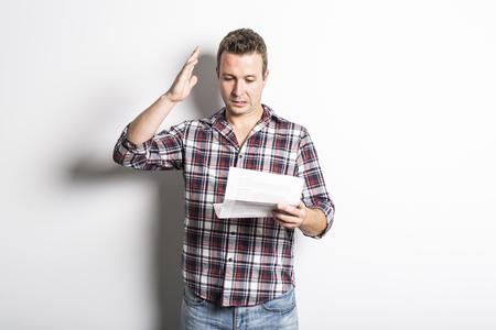 Geschokte man met een aantal documenten, geïsoleerd op een grijze achtergrond Stockfoto