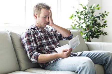 Hombre sorprendido sosteniendo algunos documentos en la sala de estar del sofá