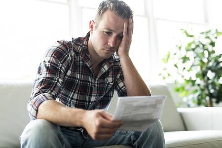 Geschokte man met een aantal documenten op de woonkamer van de bank Stockfoto