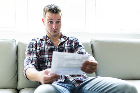 Shocked man holding some documents on sofa livingroom Banco de Imagens - 87240412