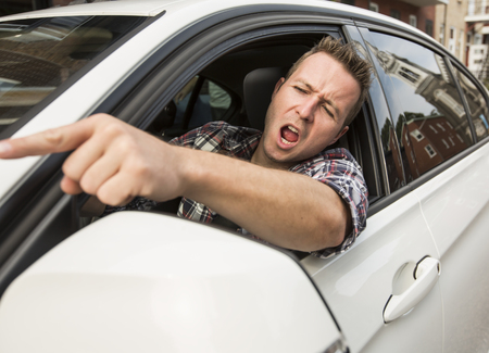 rudeness: Irritated young man driving a car. Irritated driver