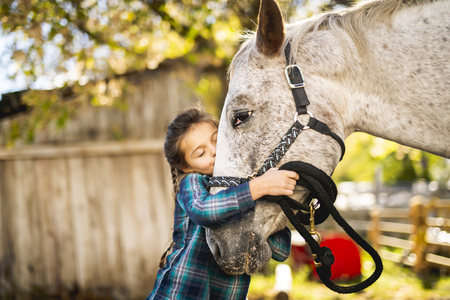 in a beautiful Autumn season of a young girl and horse