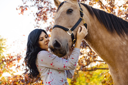 A Woman with her horse at sunset, autumn outdoors scene