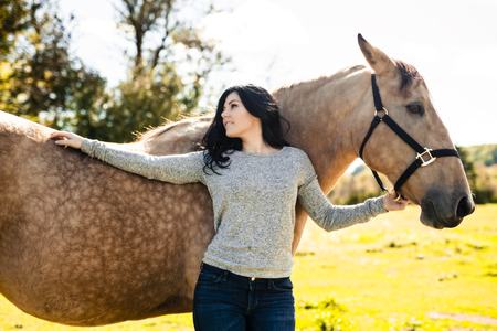 A Portrait of young beautiful woman with brown horse outdoors
